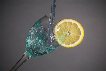 Water drops in wine glass with lemon